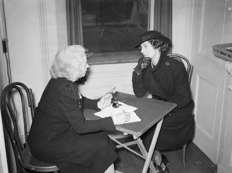 A widow of a civil servant seeks advice about her delayed pension from volunteer Mrs Wraight at the Citizens' Advice Bureau in Croydon. Mrs Wraight was one of 12 volunteers working at the bureau at this time. © IWM (D 522)