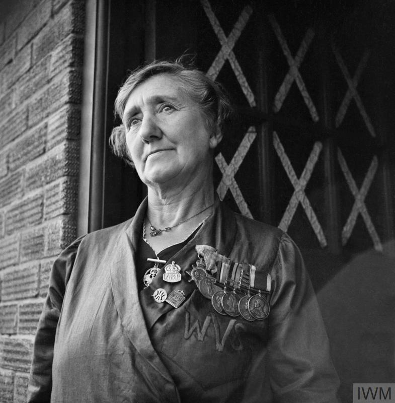 A striking portrait of villager Mrs Redmond, now a widow, who wears the medals that her late husband won during his service with the navy during the First World War. Four of her sons are serving in the navy, whilst a fifth is in the army. She 'fights' in various Civil Defence organisations, as can be seen by the Women's Voluntary Service (WVS) overall and badge and the ARP (Air Raid Precautions) badge that she wears along with the medals. Note the criss-cross of tape on the glass panes in her front door. © IWM (D 4862)